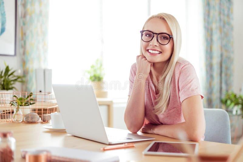 Retrato da jovem mulher de sorriso na mesa em casa imagens de stock royalty free