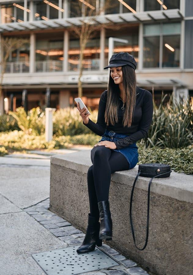 Retrato da jovem mulher de sorriso na moda que usa o telefone celular foto de stock royalty free
