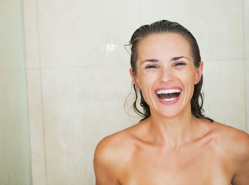Retrato da jovem mulher de sorriso no chuveiro imagem de stock