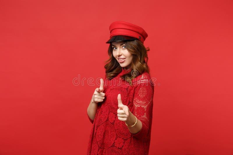 Retrato da jovem mulher de sorriso no vestido do laço, tampão apontando os indicadores na câmera isolada na parede vermelha brilh fotografia de stock royalty free
