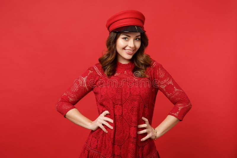 Retrato da jovem mulher de sorriso no vestido do laço, tampão que olha a posição da câmera com os braços akimbo na parede vermelh foto de stock