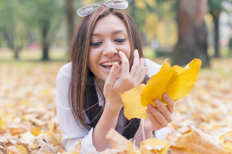 Retrato da jovem mulher de sorriso que encontra-se nas folhas de outono fotos de stock royalty free