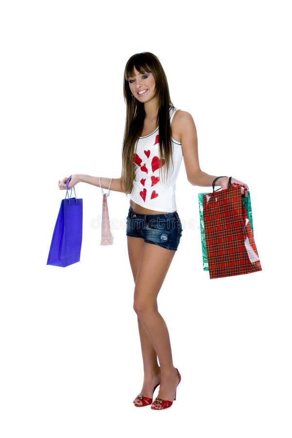 Retrato da jovem mulher de sorriso que mantém sacos de compras contra o fundo branco fotografia de stock royalty free