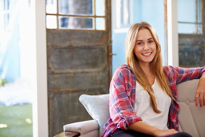Retrato da jovem mulher de sorriso que senta-se em Sofa At Home imagens de stock royalty free