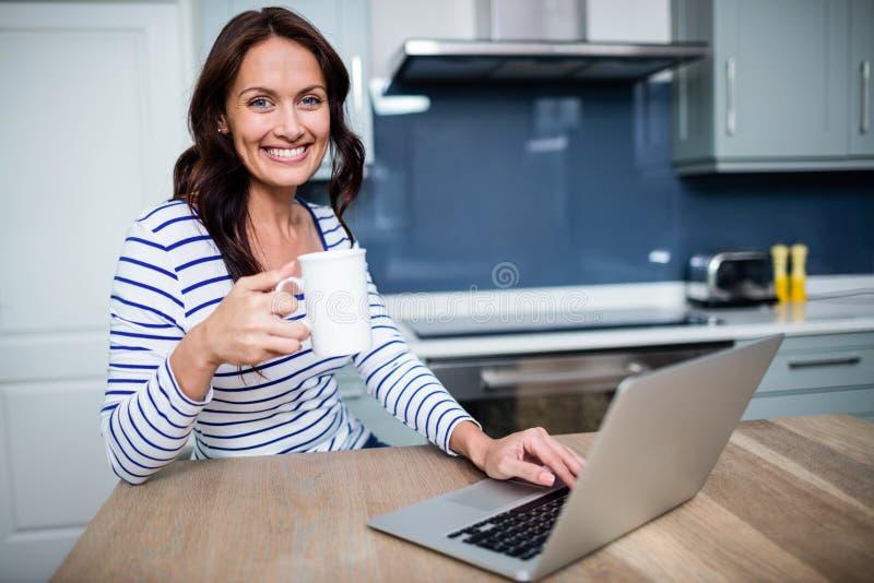 Retrato da jovem mulher de sorriso que trabalha no portátil ao guardar a caneca de café fotografia de stock