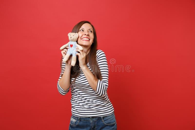 Retrato da jovem mulher de sorriso sonhadora em roupa listrada que olha mantendo o brinquedo do luxuoso do urso de peluche isolad fotografia de stock royalty free