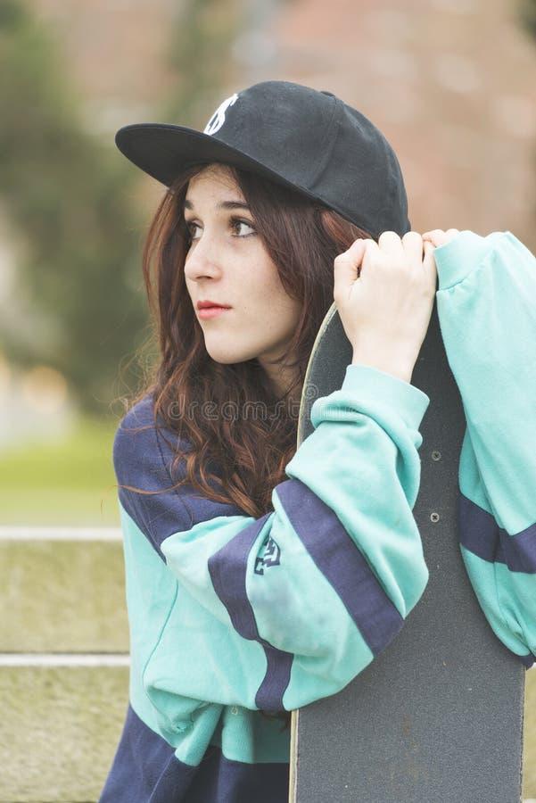 Retrato da jovem mulher do moderno com skate, estilo de vida urbano imagens de stock
