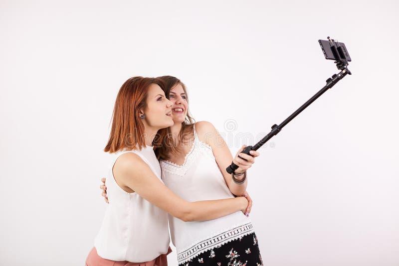Retrato da jovem mulher dois bonita que toma um selfie com uma vara do selfie imagem de stock