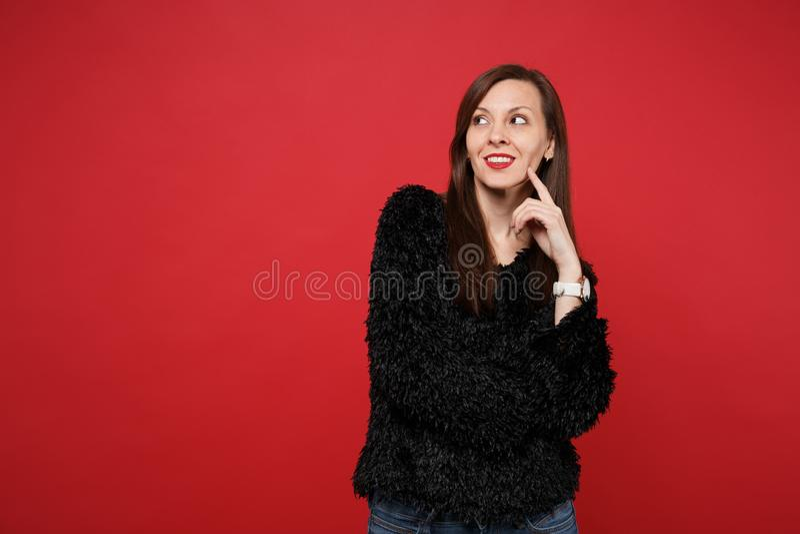 Retrato da jovem mulher dreamful na camiseta preta da pele que olha acima, pondo o dedo sobre o mordente isolado no vermelho bril fotografia de stock