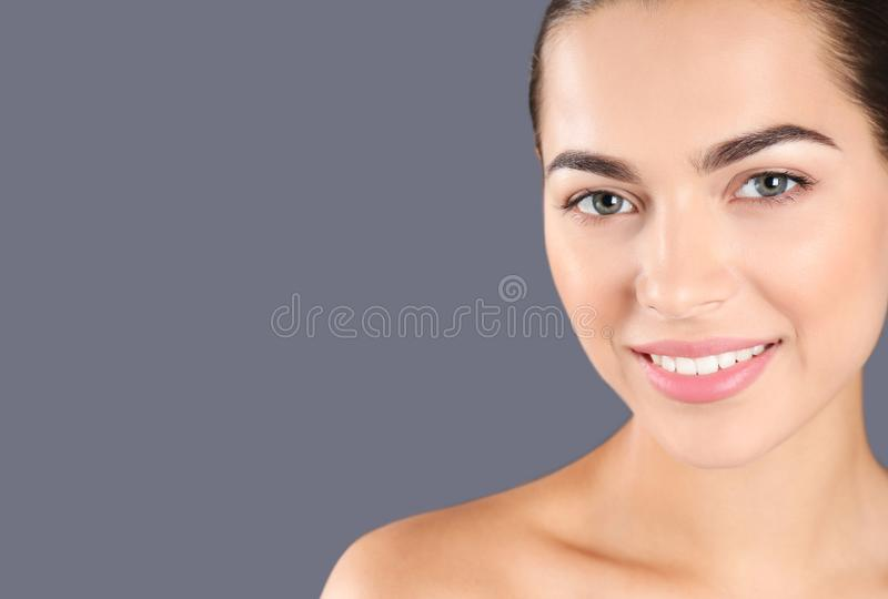 Retrato da jovem mulher e do espaço bonitos para o texto no fundo cinzento fotografia de stock royalty free