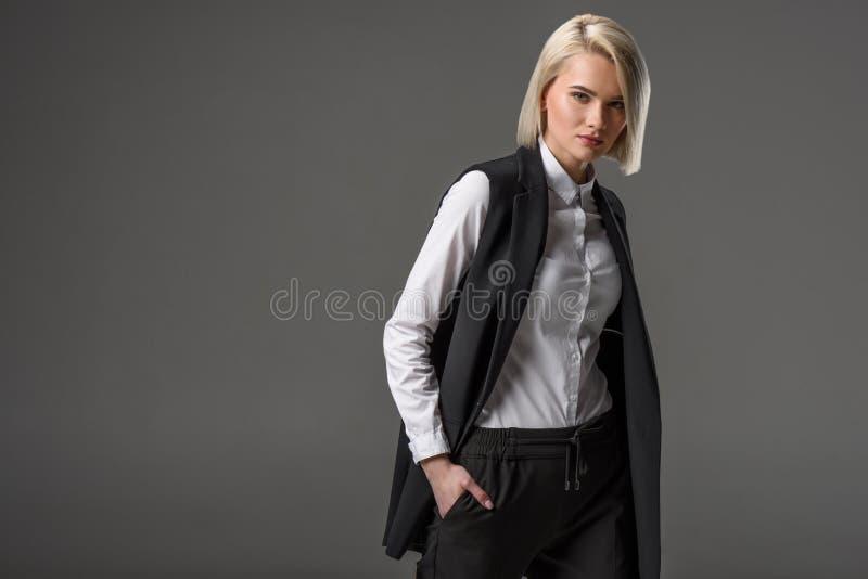 retrato da jovem mulher elegante com mãos em uns bolsos foto de stock