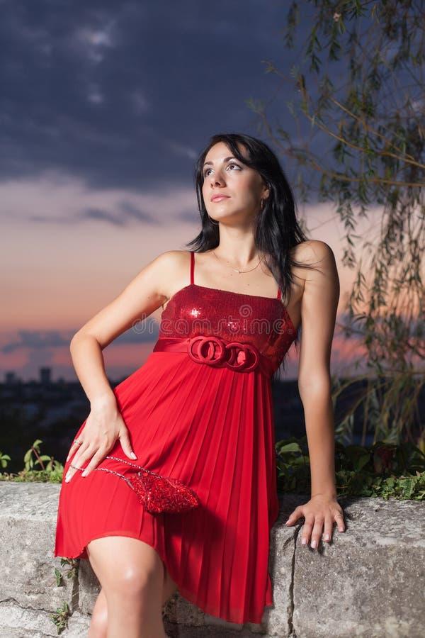 Retrato da jovem mulher em sundress vermelhos contra o céu do por do sol imagens de stock