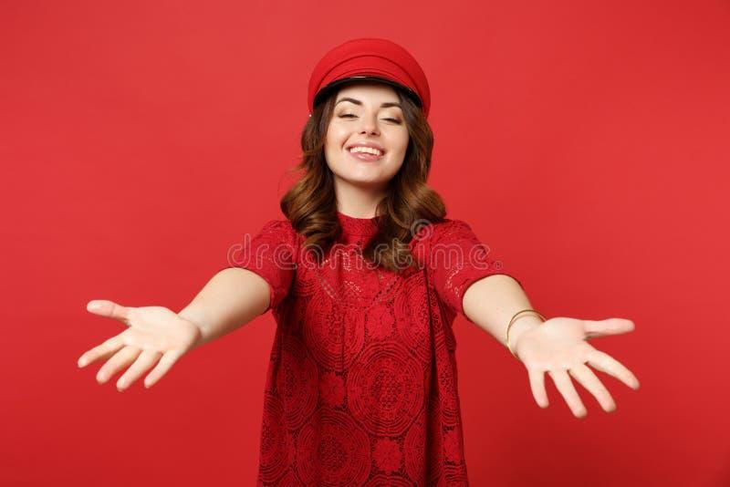 Retrato da jovem mulher encantador de sorriso no tampão do vestido do laço que está com as mãos estendidos isoladas no vermelho b fotografia de stock