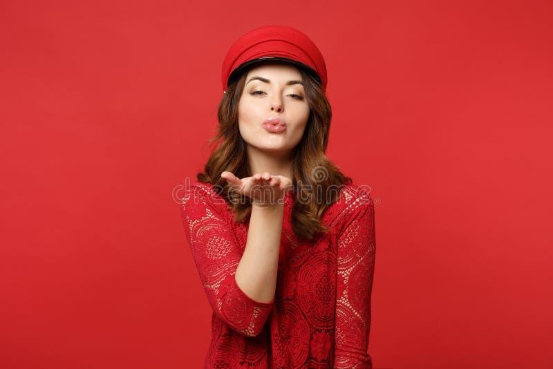 Retrato da jovem mulher encantador impressionante no vestido do laço, tampão que funde enviando o beijo do ar na parede vermelha  fotos de stock royalty free