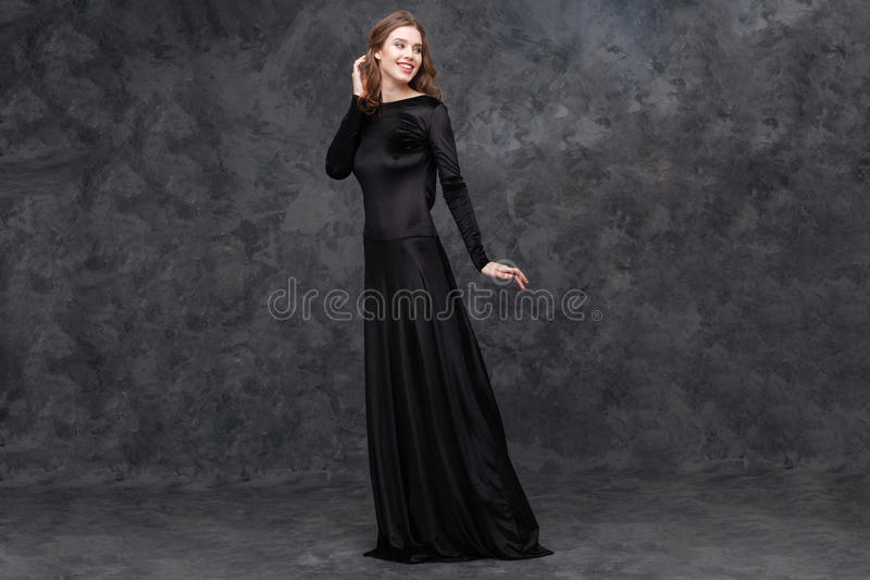 Retrato da jovem mulher encantador no vestido preto longo imagens de stock royalty free