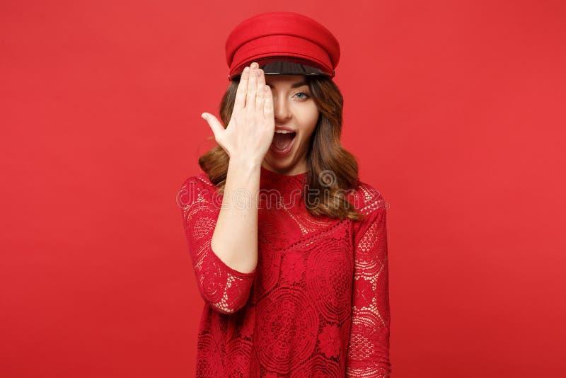 Retrato da jovem mulher engraçada no tampão do vestido do laço que mantém a boca aberta, cobrindo a cara com a palma isolada no v imagem de stock