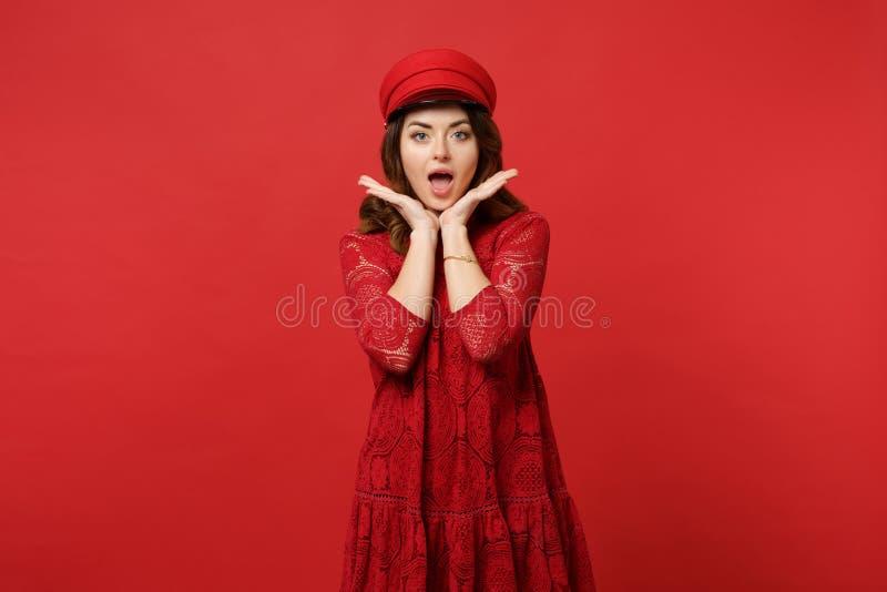 Retrato da jovem mulher entusiasmado no vestido do laço, mão da terra arrendada do tampão perto da cara que mantém a boca aberta  foto de stock