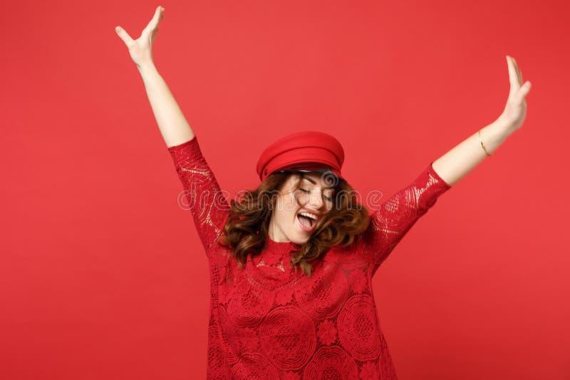 Retrato da jovem mulher feliz alegre no vestido do laço, tampão que salta com as mãos de espalhamento isoladas na parede vermelha foto de stock