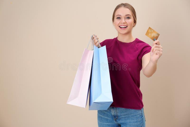 Retrato da jovem mulher feliz com cartão de crédito e dos sacos de compras no fundo da cor, espaço para o texto fotografia de stock royalty free