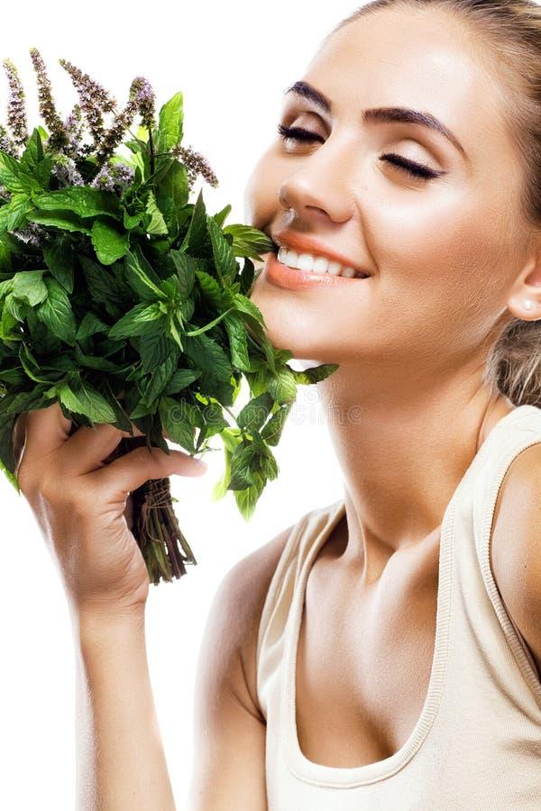 Retrato da jovem mulher feliz com um pacote de hortelã fresca fotografia de stock royalty free