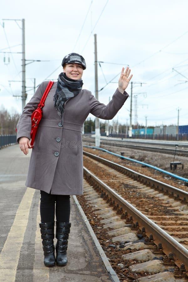 Retrato da jovem mulher feliz da forma que está na estação de trem fotos de stock