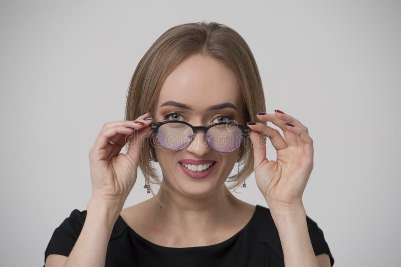 Retrato da jovem mulher feliz em espetáculos à moda imagem de stock royalty free