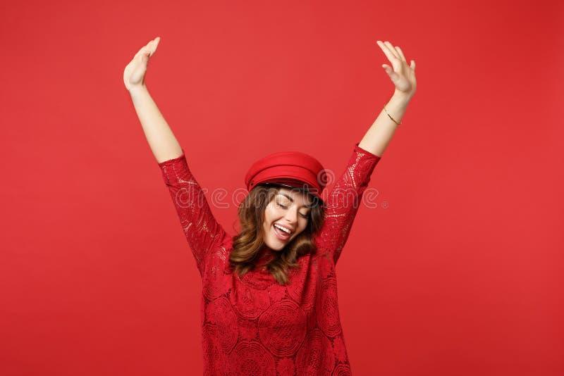 Retrato da jovem mulher feliz no vestido do laço, tampão que mantém os olhos mãos fechados e aumentando na parede vermelha brilha imagens de stock royalty free