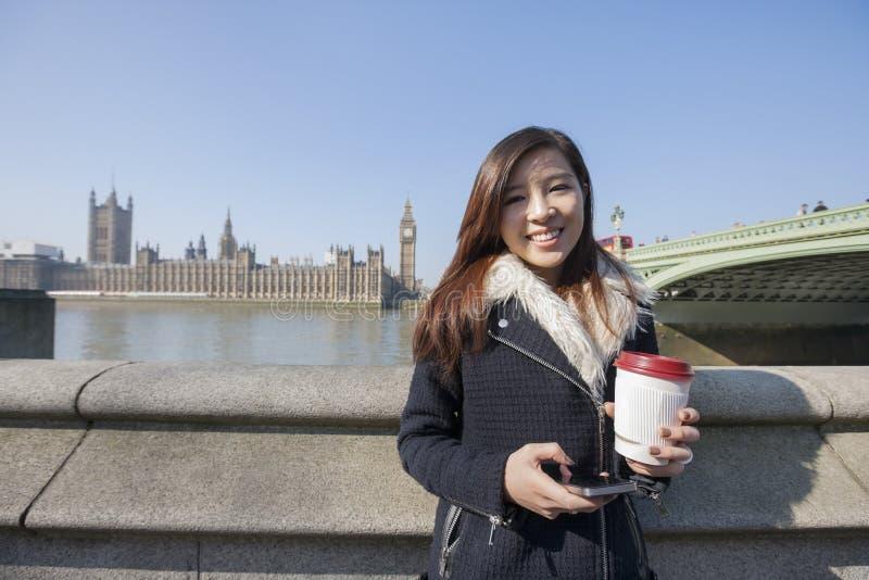 Retrato da jovem mulher feliz que mantém o telefone celular e o copo descartável contra Big Ben em Londres, Inglaterra, Reino Uni imagem de stock royalty free