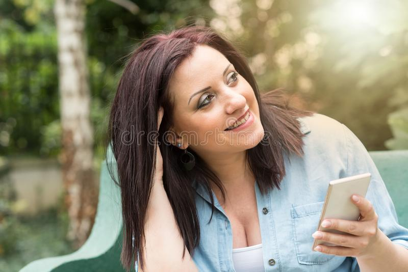 Retrato da jovem mulher feliz que usa seu telefone celular, efeito da luz foto de stock
