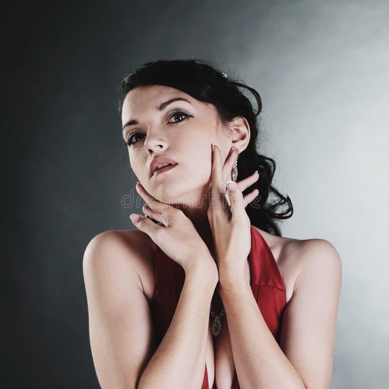 Retrato da jovem mulher glamoroso em um vestido vermelho imagem de stock
