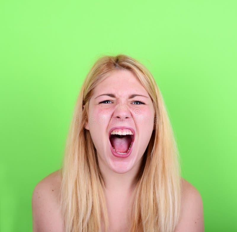 Retrato da jovem mulher loura desesperada que grita contra o verde fotografia de stock