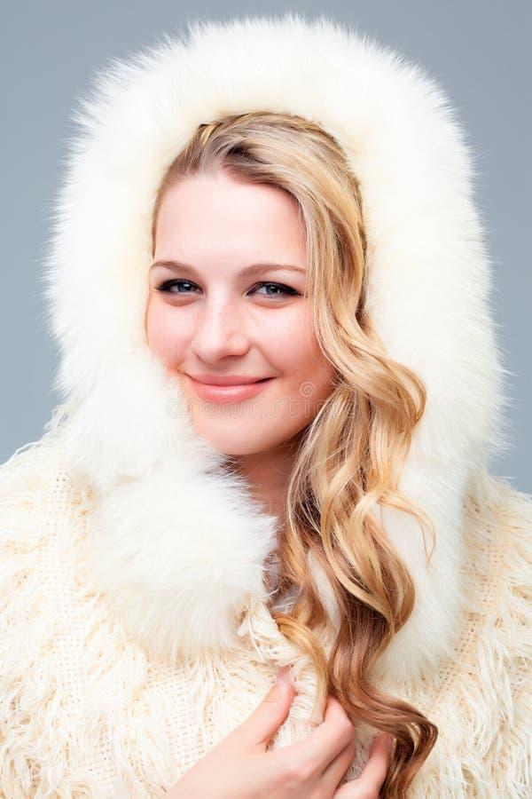 Retrato da jovem mulher loura no casaco de pele fotografia de stock