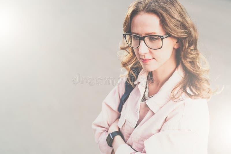 Retrato da jovem mulher A menina do moderno nos vidros e no revestimento cor-de-rosa da sarja de Nimes está na rua da cidade e em fotografia de stock royalty free