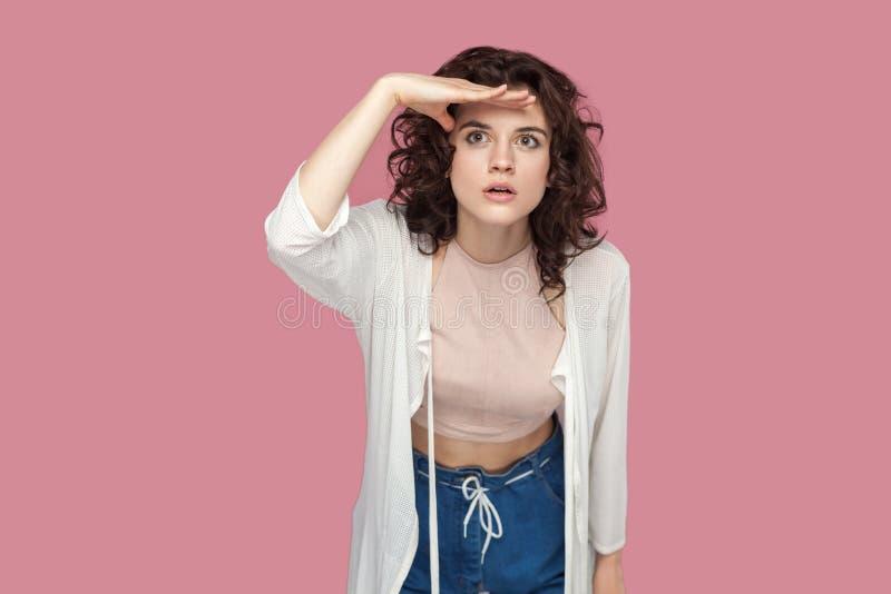 Retrato da jovem mulher moreno bonita atenta séria com penteado encaracolado no estilo ocasional que está com mão na testa fotos de stock royalty free