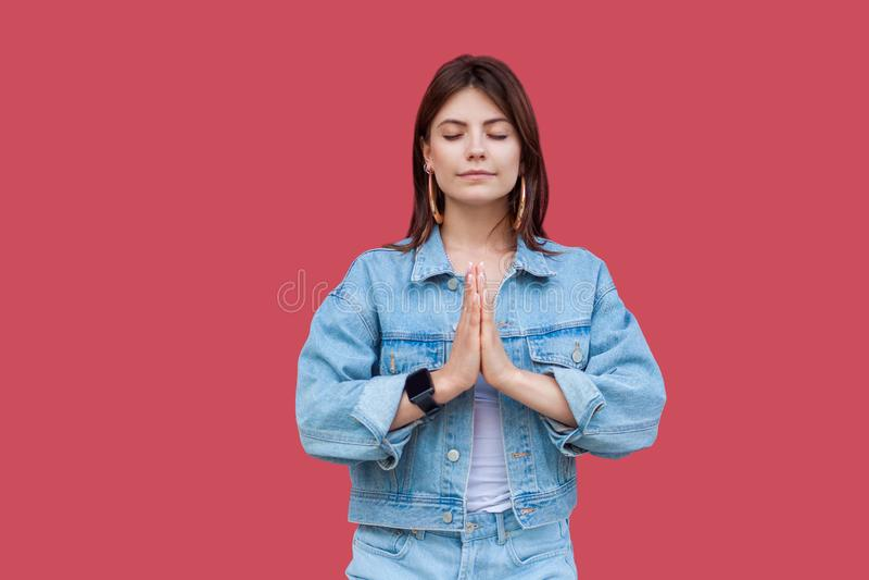 Retrato da jovem mulher moreno bonita calma com composição na posição do estilo ocasional da sarja de Nimes com mãos da palma e e imagens de stock