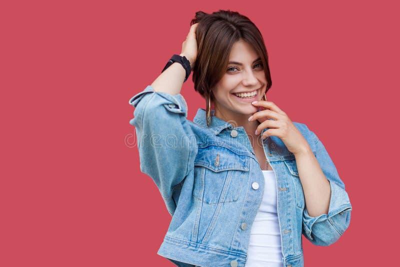 Retrato da jovem mulher moreno bonita extravagante com composição na posição do estilo ocasional da sarja de Nimes que guarda seu foto de stock royalty free