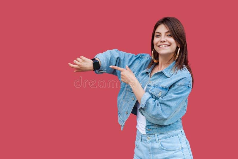 Retrato da jovem mulher moreno bonita feliz com composição na exibição da posição do estilo ocasional da sarja de Nimes e de apon fotografia de stock royalty free