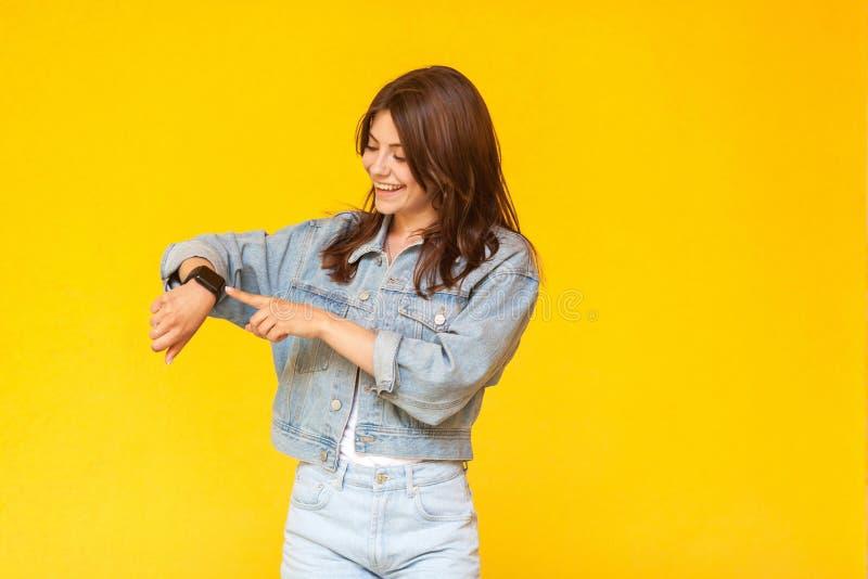 Retrato da jovem mulher moreno bonita feliz na posição do estilo ocasional da sarja de Nimes, no sorriso toothy, em tocá-la e em  imagem de stock