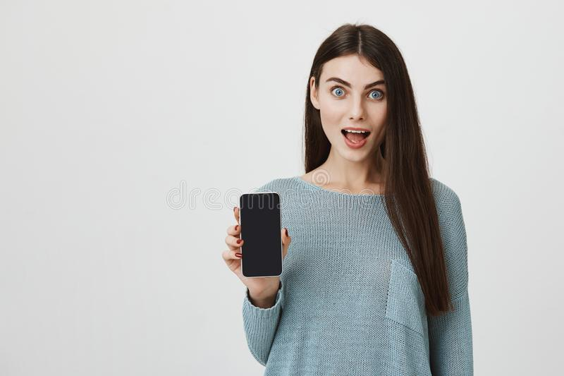 Retrato da jovem mulher moreno entusiasmado com os olhos estalados que mostram a tela do telefone em choque com terra arrendada a fotos de stock royalty free