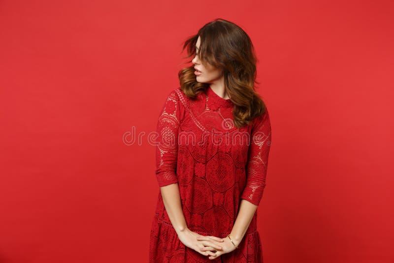 Retrato da jovem mulher moreno na posição do vestido do laço com o cabelo de lado de vibração da mão isolado na parede vermelha b foto de stock royalty free