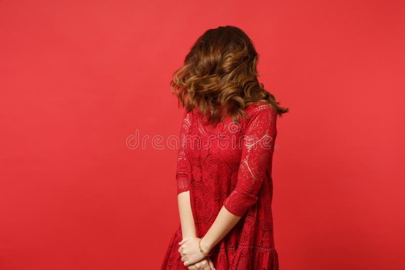 Retrato da jovem mulher moreno na posição do vestido do laço, saltando com o cabelo de vibração isolado na parede vermelha brilha imagens de stock royalty free