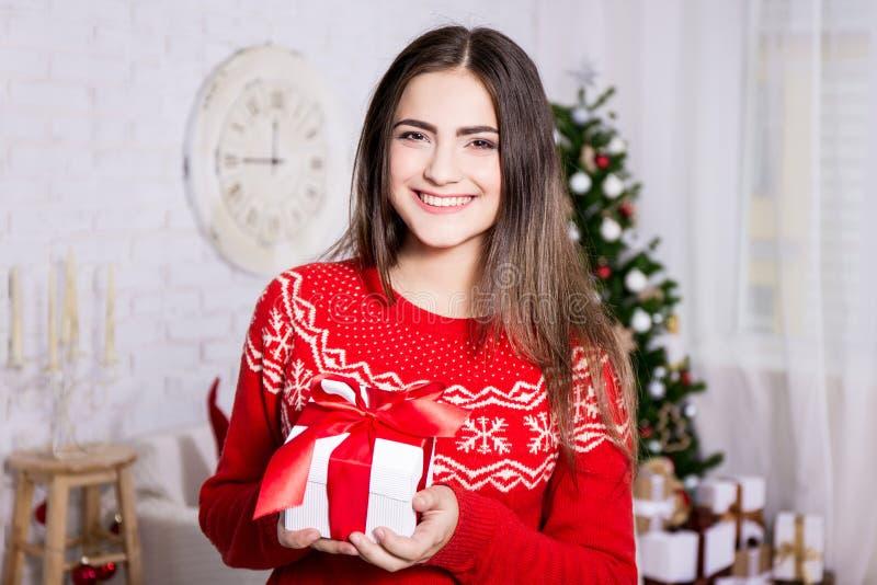 Retrato da jovem mulher na sala de visitas decorada com presentes e fotos de stock royalty free