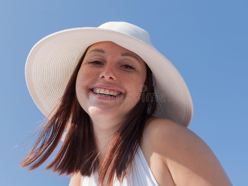 Retrato da jovem mulher no chapéu branco contra o céu claro fotografia de stock