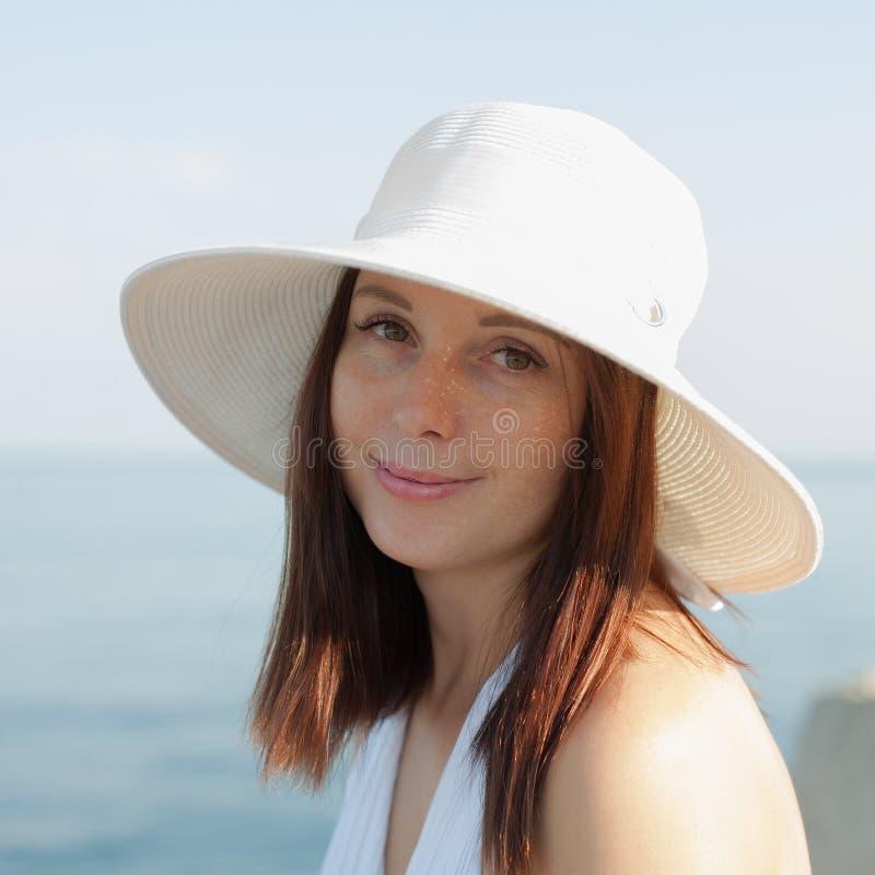 Retrato da jovem mulher no chapéu branco contra o mar imagem de stock royalty free