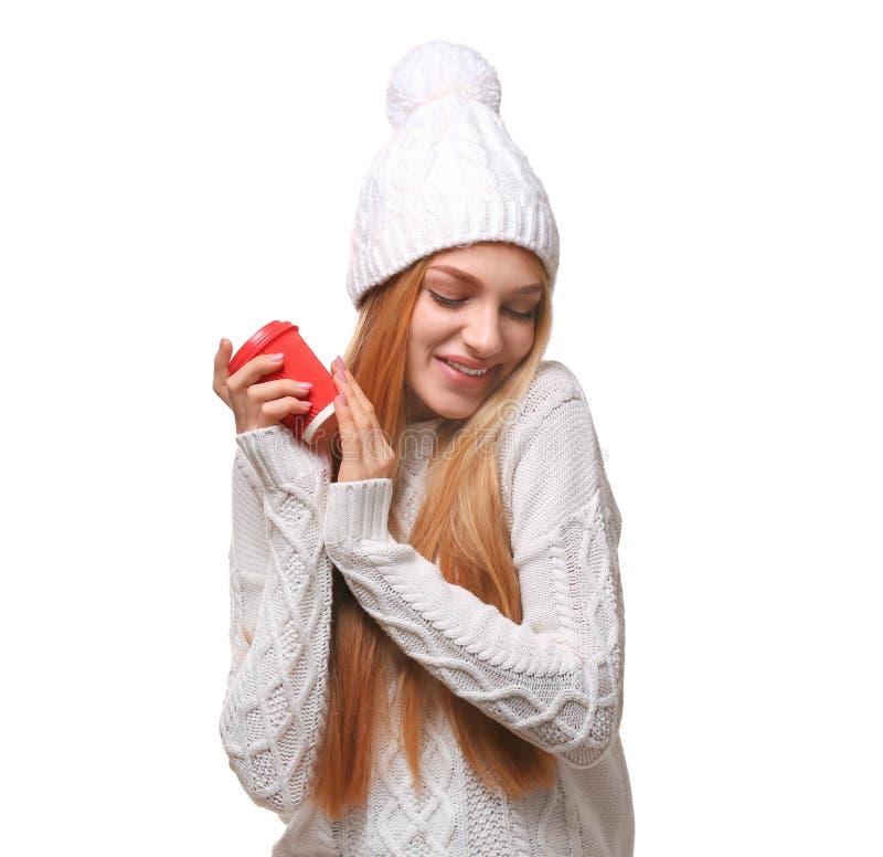 Retrato da jovem mulher no chapéu e na camiseta à moda com o copo de papel do café no fundo branco imagem de stock royalty free