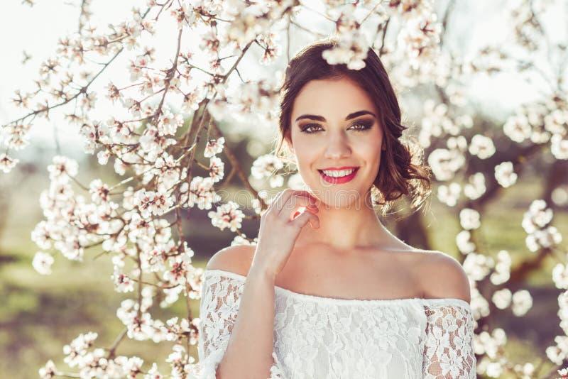 Retrato da jovem mulher no jardim florescido na primavera tim imagens de stock royalty free