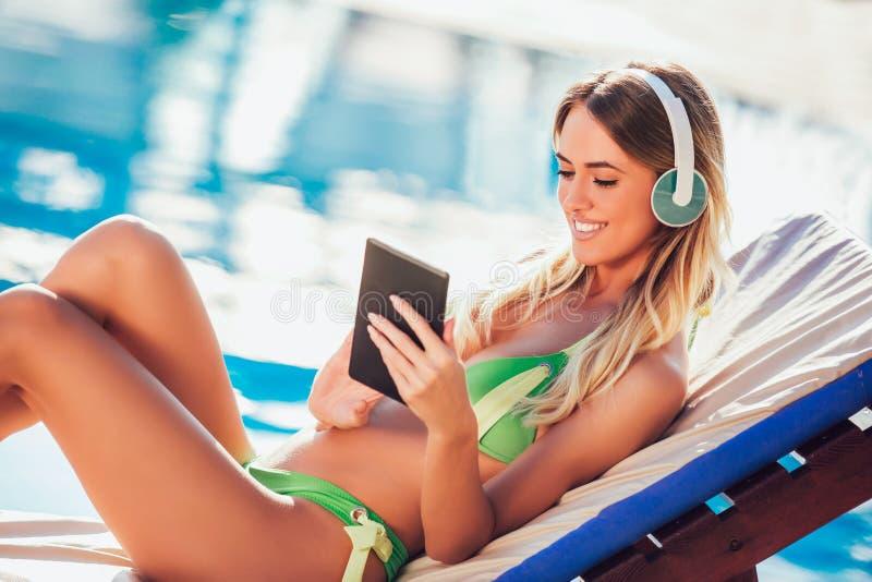 Retrato da jovem mulher no sol tropical perto da piscina foto de stock