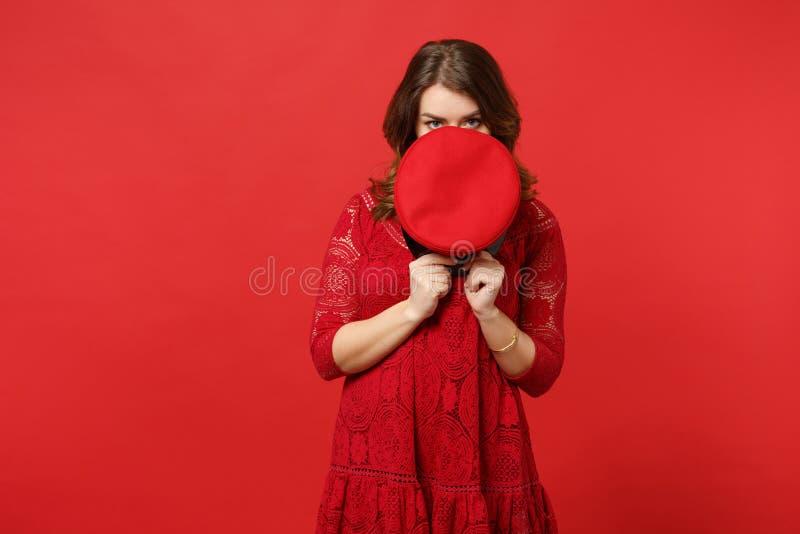 Retrato da jovem mulher no vestido do laço que esconde, cobrindo a cara com o tampão, olhando a câmera isolada na parede vermelha imagens de stock royalty free