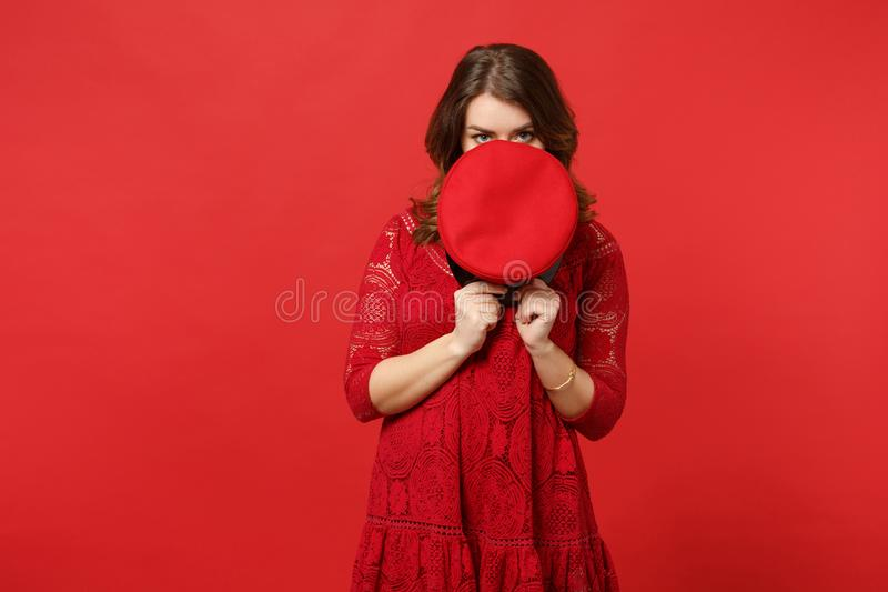 Retrato da jovem mulher no vestido do laço que esconde, cobrindo a cara com o tampão, olhando a câmera isolada na parede vermelha foto de stock