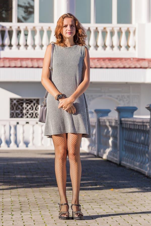 Retrato da jovem mulher no vestido sem mangas cinzento no parque imagens de stock